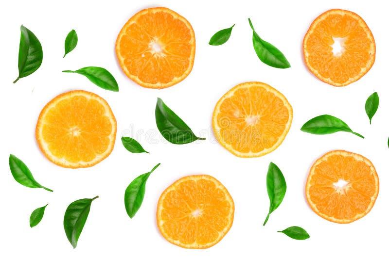 Куски апельсина или tangerine украшенных при листья зеленого цвета изолированные на белой предпосылке, взгляд сверху Состав плодо стоковое изображение