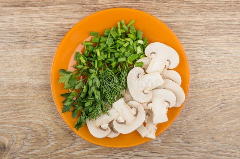 Куски грибов, петрушки, укропа и зеленого лука в плите стоковые фото