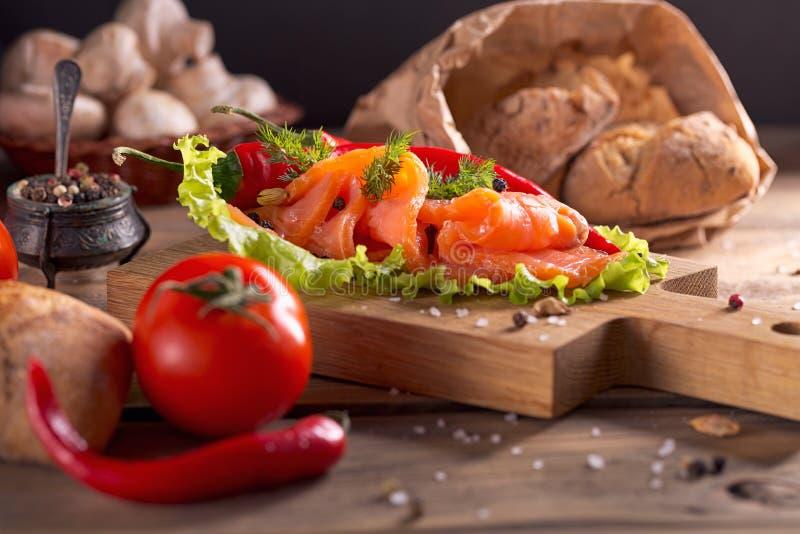 Куски копченых семг с укропом, перцем chile, томатами и br стоковая фотография