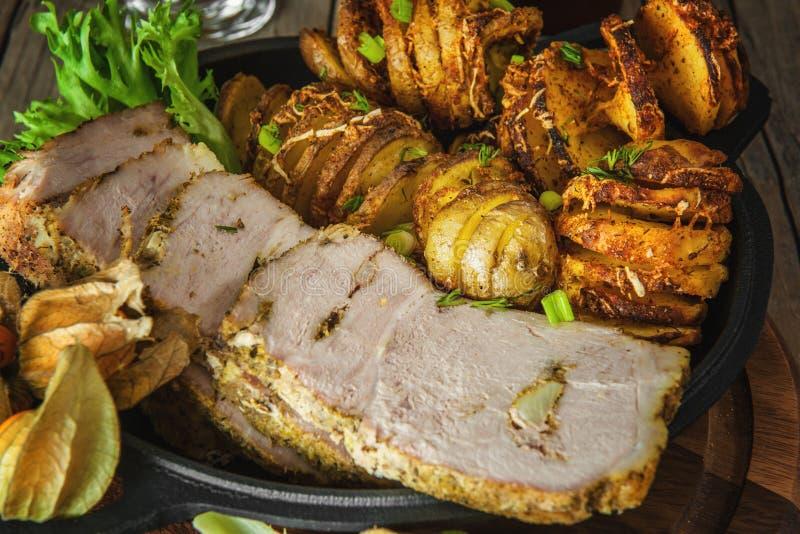 Куски отрезанного отрезанного испеченного tenderloin свинины с зажаренными спиральными картошками стоковое фото