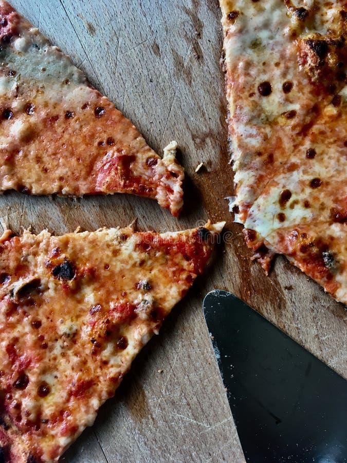 Куски пиццы на деревянной плите стоковое фото