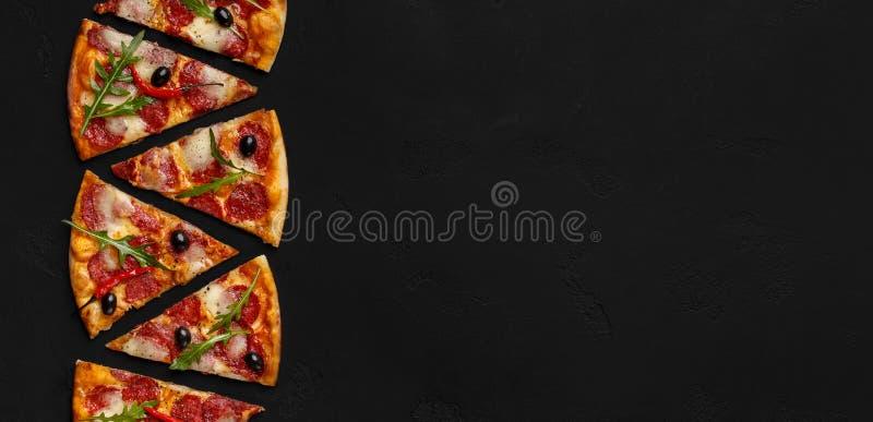 Куски пиццы с салатом салями и ракеты на черной предпосылке стоковая фотография rf