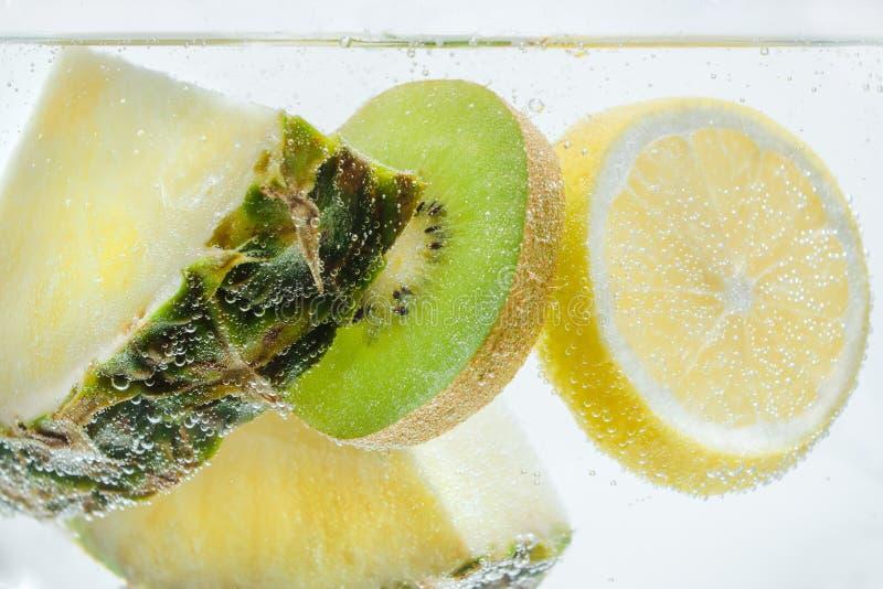 Куски свежих ананаса, лимона и кивиа в ясной чистой воде стоковые фотографии rf