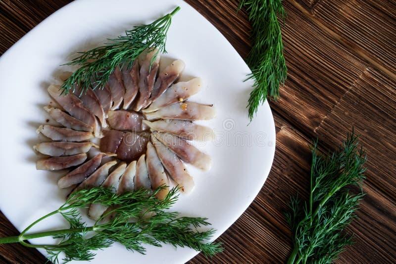 Куски скандинавских сельдей со специями и укропом в белой плите стоковые фото