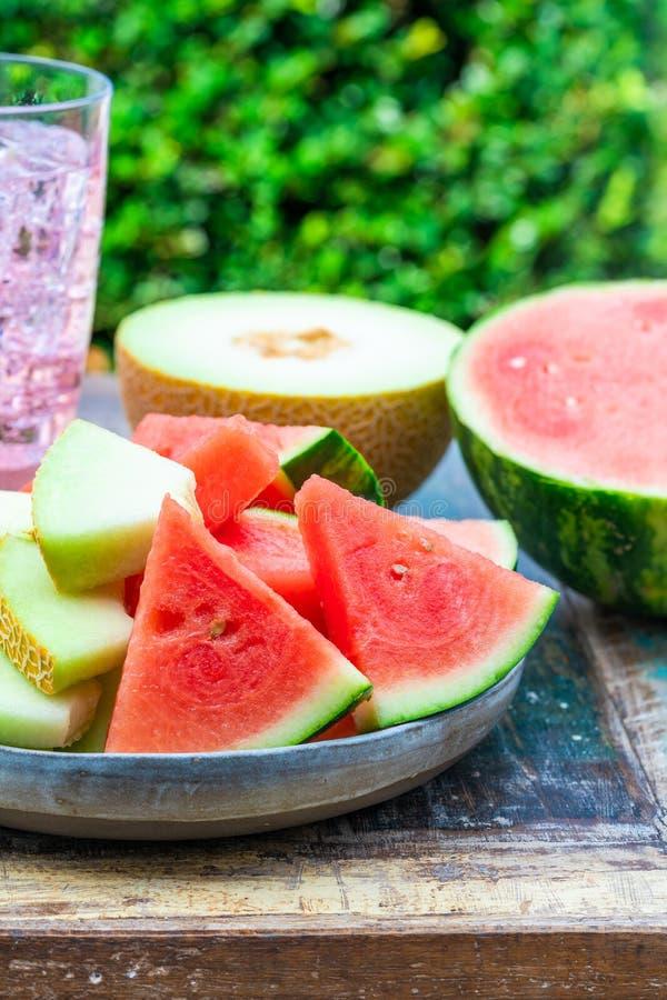 Куски сладостных, освежая арбуза и дыни honeydew на таблице сада стоковое изображение