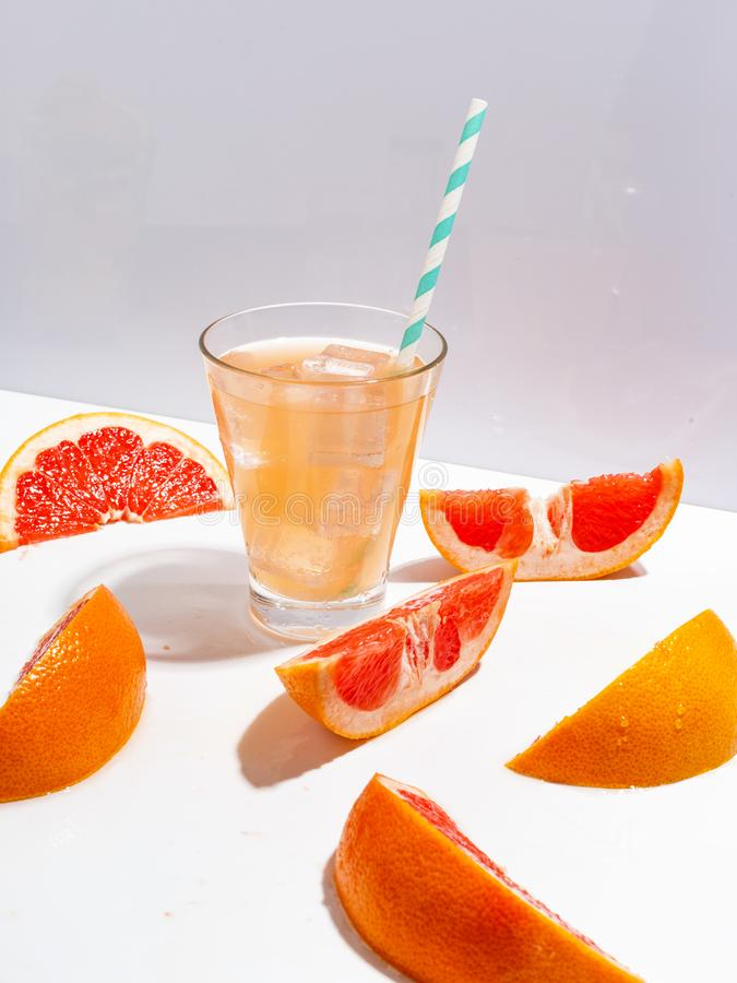 Куски сочного грейпфрута и стекла свежего лимонада с льдом на белой предпосылке стоковая фотография