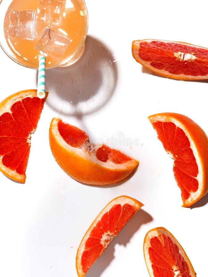 Куски сочного грейпфрута и стекла свежего лимонада с льдом на белой предпосылке стоковое фото