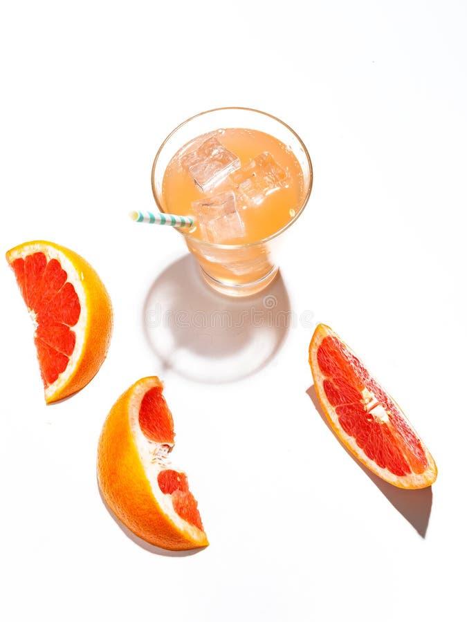 Куски сочного грейпфрута и стекла свежего лимонада с льдом на белой предпосылке стоковая фотография rf