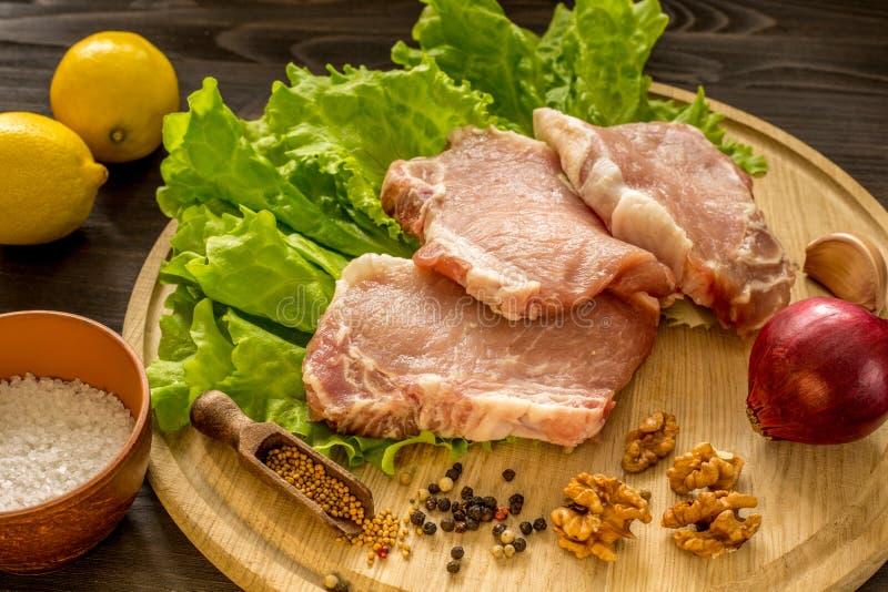 Куски сырого мяса Escalope свинины на деревянной доске стоковое фото rf