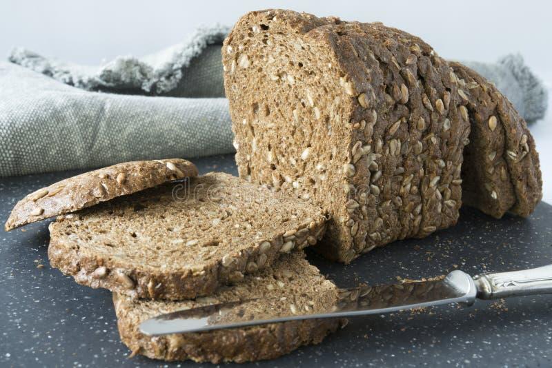 Куски хлеба всего зерна коричневого с семенами подсолнуха, на серой разделочной доске стоковая фотография rf