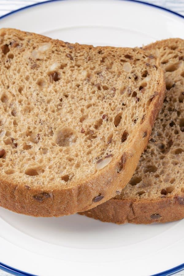 Куски хлеба зерна с прессформой На белой плите с голубой нашивкой На деревянном столе стоковая фотография