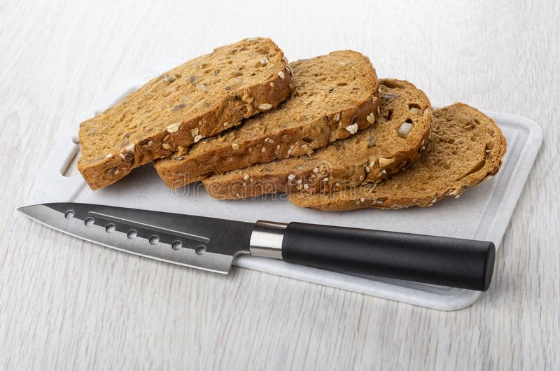 Куски хлеба с различными семенами, candied плодами, отрубями рож, кухонным ножом на разделочной доске на таблице стоковое фото rf