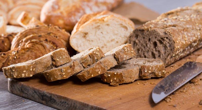 Куски wheaten хлеба и ножа на деревянной поверхности стоковое фото rf