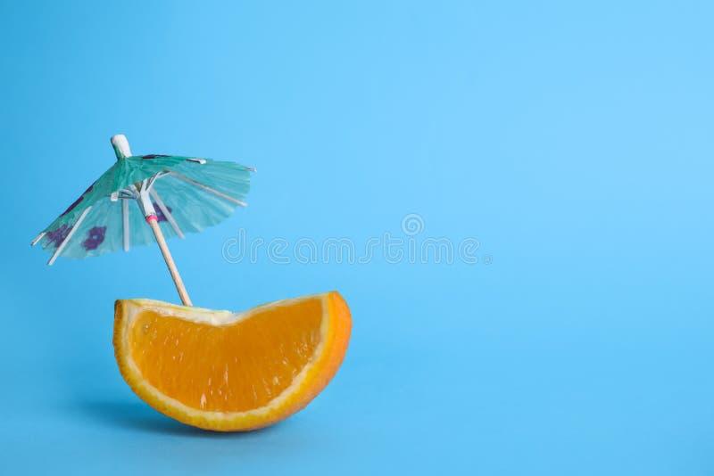 Кусок апельсина с зонтиком коктейля на предпосылке цвета стоковое фото