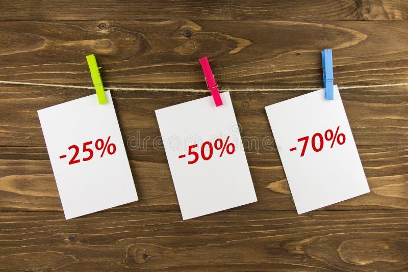Кусок бумаги на зажимке для белья на деревянной предпосылке Уцененное цена стоковые изображения
