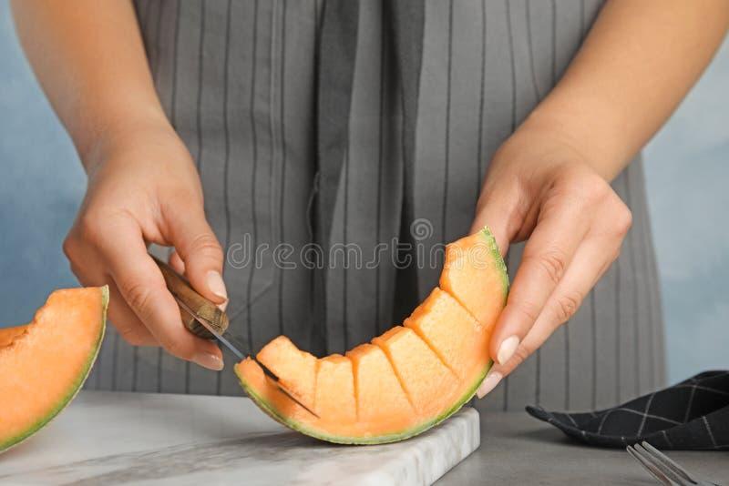 Кусок дыни канталупы вырезывания молодой женщины на таблице стоковое фото rf