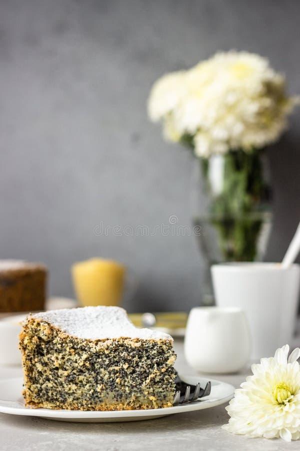 Кусок макового семенного торта с порошковым сахаром, кремом и чашкой кофе стоковое фото rf