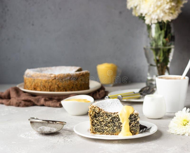 Кусок макового семенного торта с порошковым сахаром, кремом и чашкой кофе стоковая фотография rf