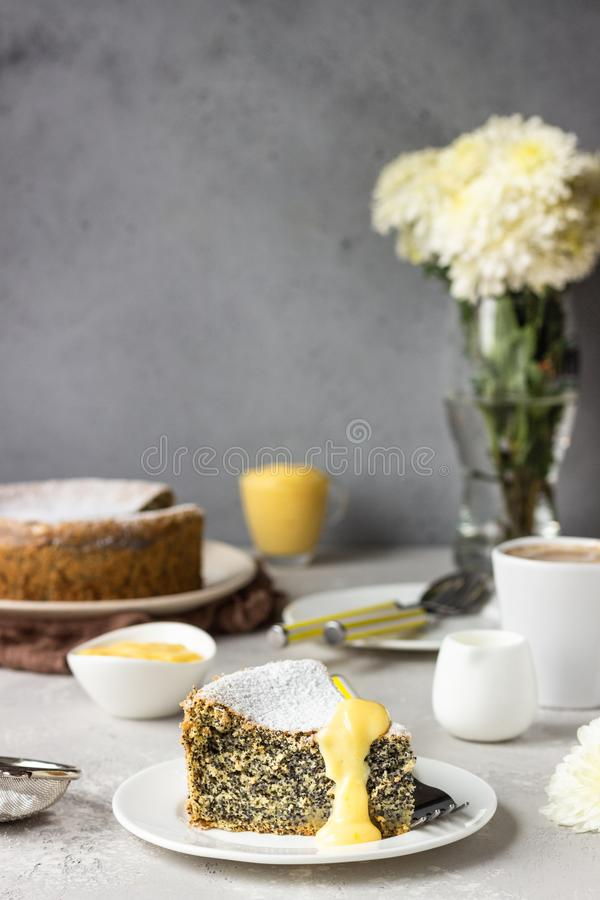Кусок макового семенного торта с порошковым сахаром, кремом и чашкой кофе стоковые фото