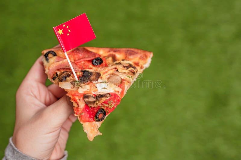 Кусок пиццы в женских руках с китайским флагом в форме зубочистки Обед на зеленой траве r r стоковые фотографии rf