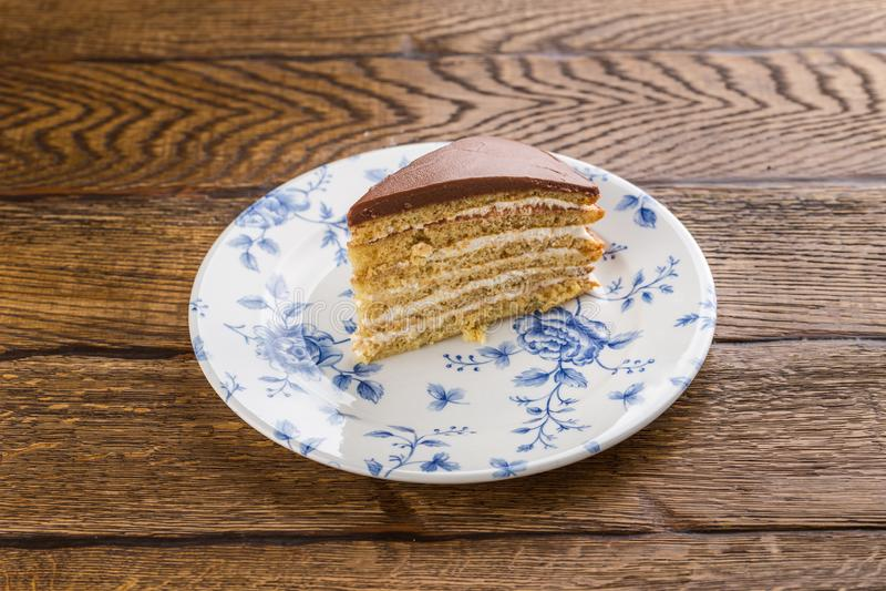 Кусок торта миндалины с замороженностью шоколада изолированной на деревянной предпосылке стоковые изображения rf