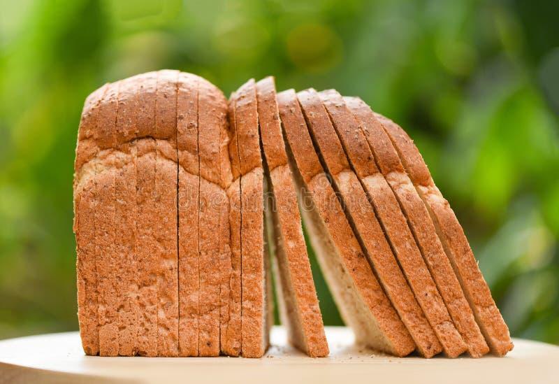 Кусок хлеба на деревянной предпосылке зеленого цвета разделочной доски и природы в утре на завтрак стоковое фото rf