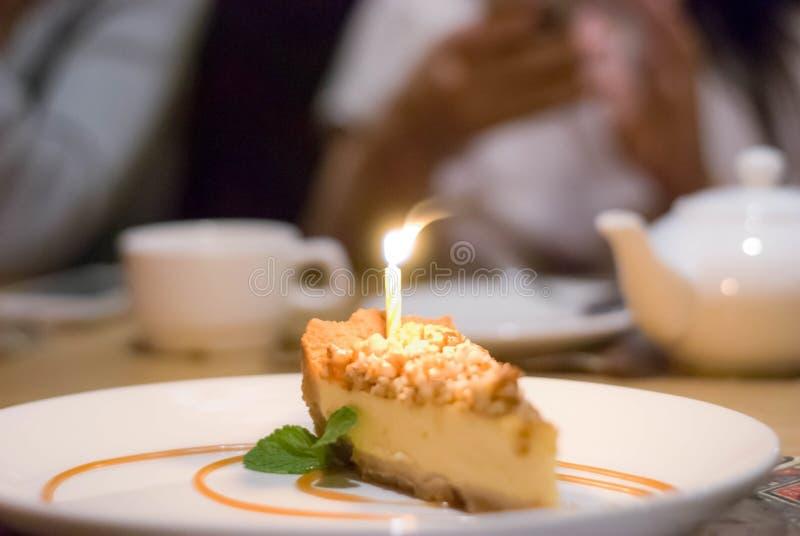 Кусок чизкейка с горящей свечой для дня рождения стоковая фотография rf