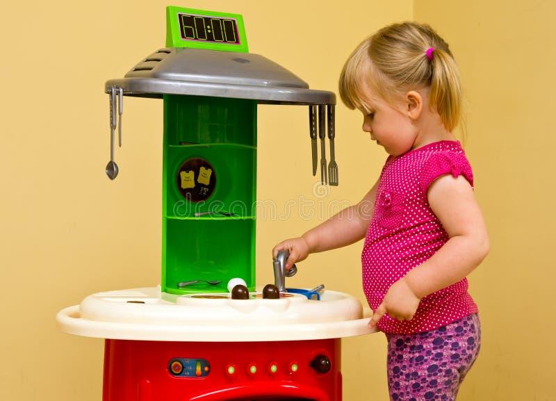 Кухня девушки и игрушки стоковые изображения