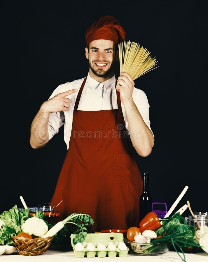Кухня и концепция варить Кашевар работает в кухне около таблицы с овощами и инструментами стоковое изображение rf