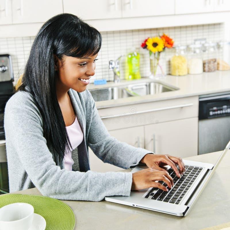 кухня компьютера используя детенышей женщины стоковые фото