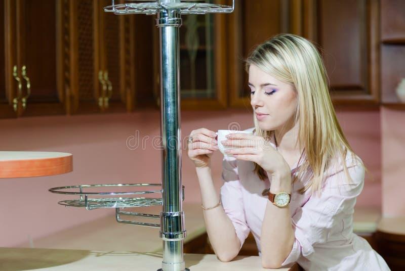 Кухня кофе молодой женщины выпивая на дому стоковая фотография