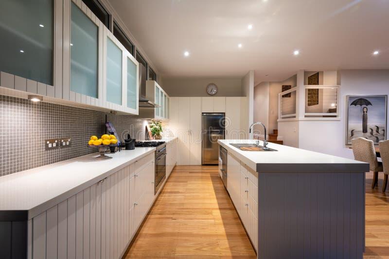 Кухня роскошного отечественного дома жилая с верхними частями стенда гранита, шкафами, крыть черепицей черепицей задней частью вы стоковые изображения