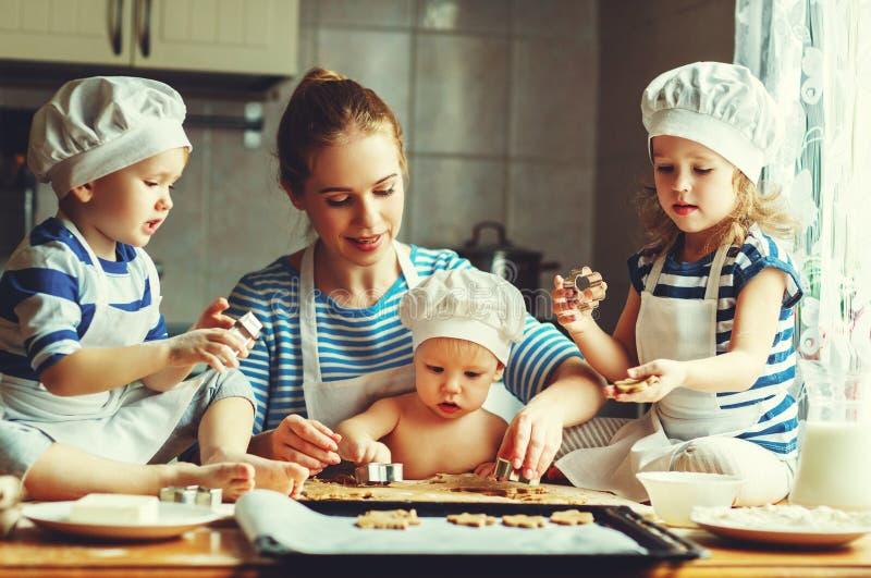 кухня семьи счастливая мать и дети подготавливая тесто, ба стоковые фото