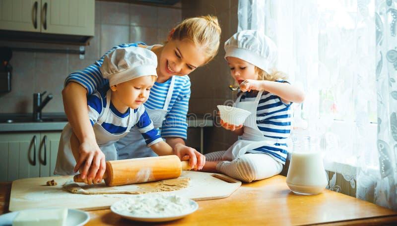 кухня семьи счастливая мать и дети подготавливая тесто, ба стоковое фото