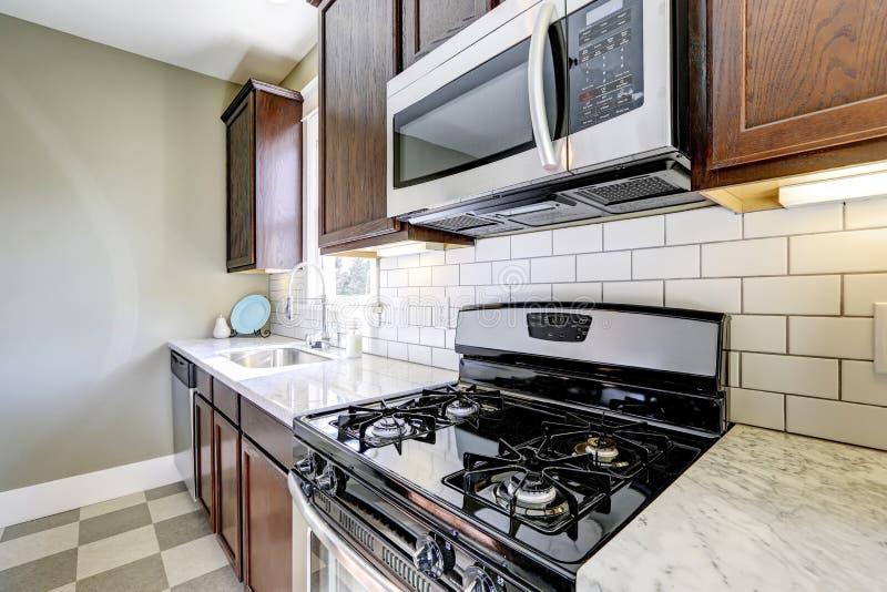 Кухня с мраморными верхними частями и задней частью плитки брызгает отделку стоковая фотография