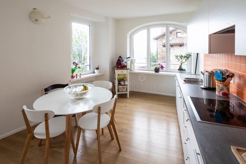 Кухня с оранжевыми плитками и современной таблицей Большое окно с взглядом стоковое изображение