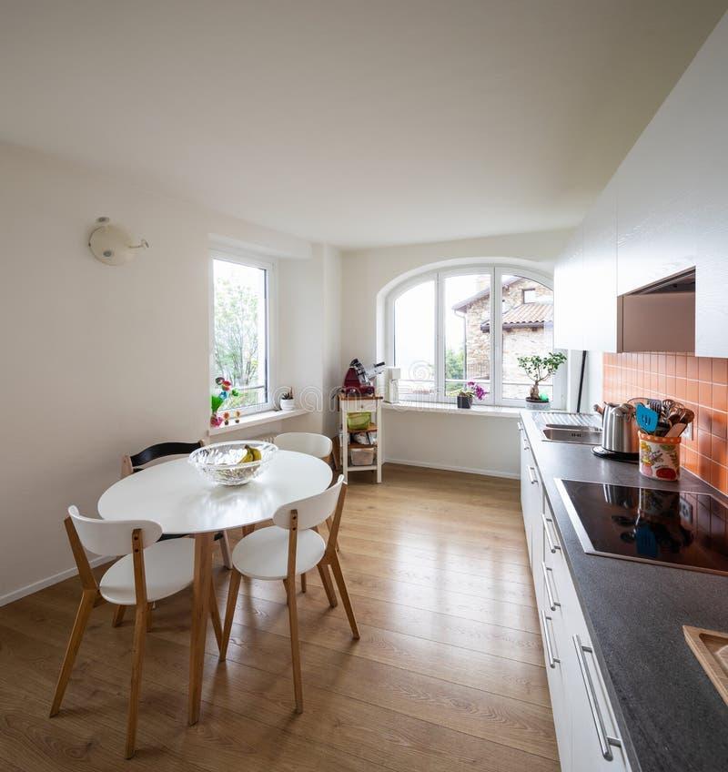 Кухня с оранжевыми плитками и современной таблицей Большое окно с взглядом стоковое изображение rf