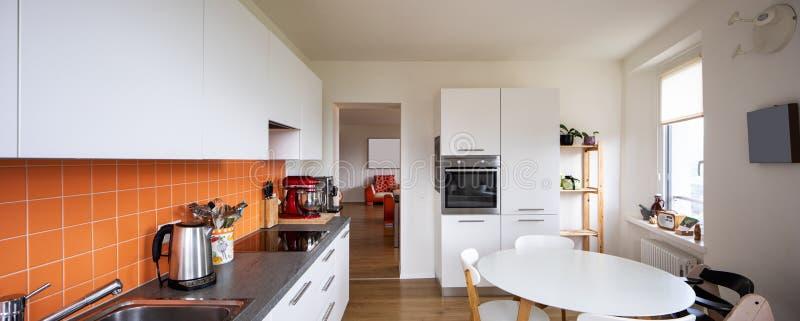 Кухня с оранжевыми плитками и современной таблицей Большое окно с взглядом стоковое фото rf