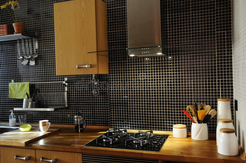 Кухня с черными плитками и естественным деревянным счетчиком стоковые фотографии rf