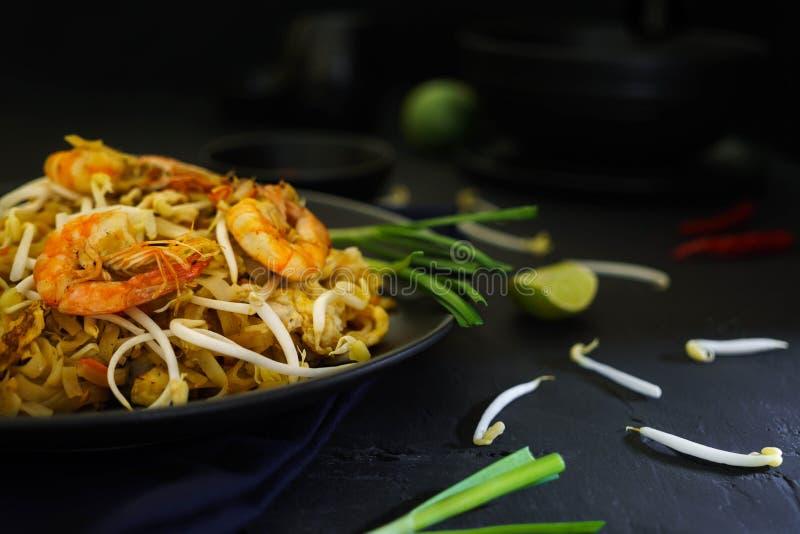 Кухня Таиланда традиционная, прокладывает тайскую, высушенную лапшу, зажаренные лапши, креветку и морепродукты, еду улицы, темную стоковые фотографии rf