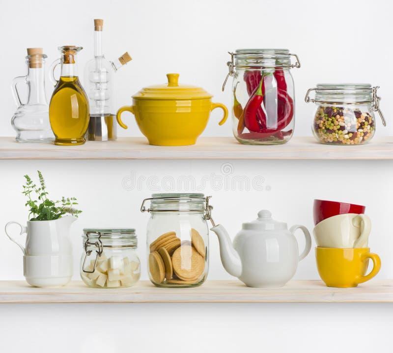 Кухня shelves с различными пищевыми ингредиентами и утварями на белизне стоковая фотография rf