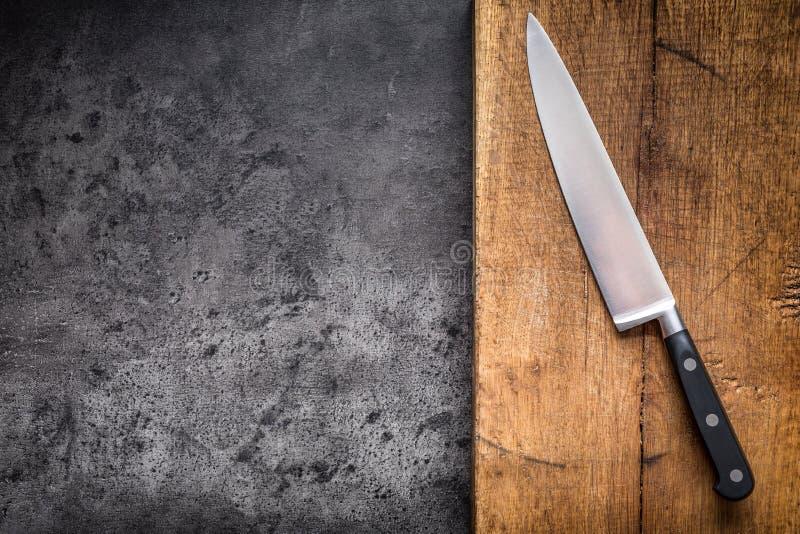 Кухонный нож на конкретной или деревянной доске стоковое изображение