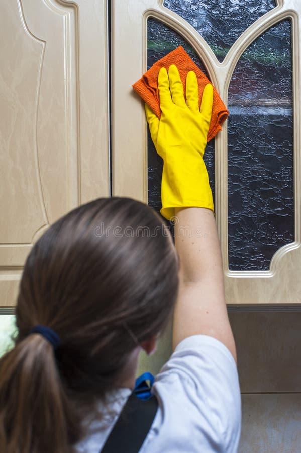 Кухонный шкаф кухни женщины scrubbing с ветошью стоковое фото rf
