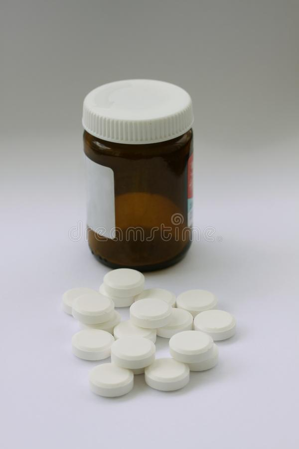 Куча белых пилюлек с коричневой бутылкой пилюльки в бутылке backgroundll иллюстрируя витамины или наркоманию к лекарствам конец в стоковое фото