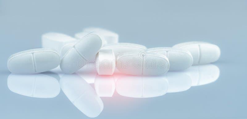 Куча белых продолговатых таблеток планшетов на предпосылке градиента Белые антибиотические таблетки планшета Фармацевтическая про стоковые изображения