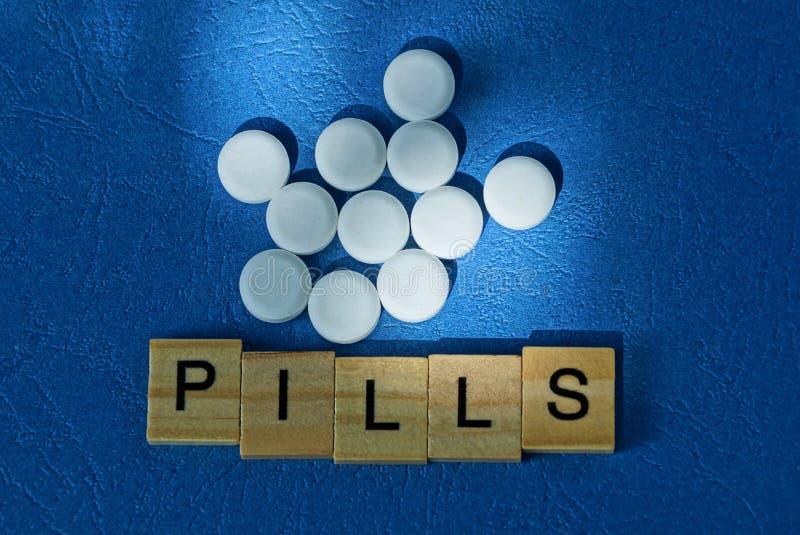 Куча белых таблеток и слово от деревянных писем стоковые изображения rf