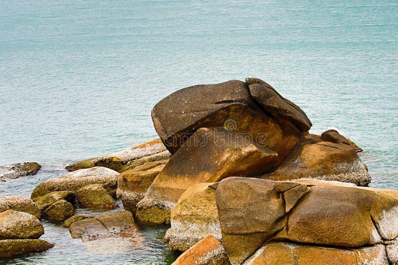 Куча берега загубленного камнями скалистого выдержала большая в пляже голубого дизайна основания океана открытого моря диком стоковые фото
