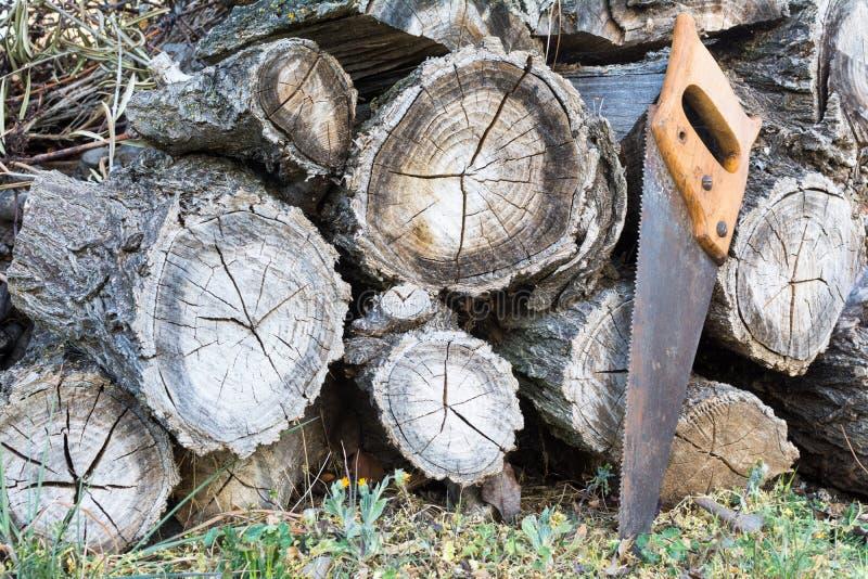 Куча деревянного пиломатериала и старой ручной пилы стоковые изображения rf