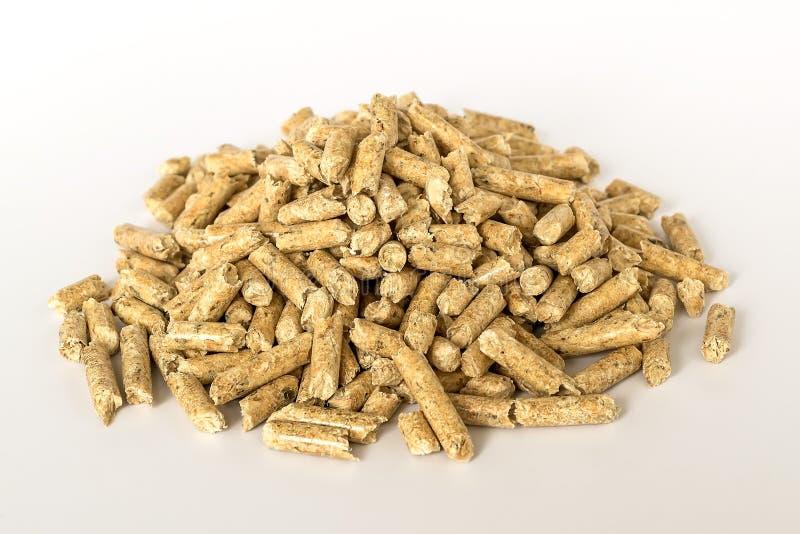Куча деревянных лепешек на белой предпосылке Альтернативное биотопливо от опилк для гореть в печах и плитах Кот и хомяк стоковое изображение