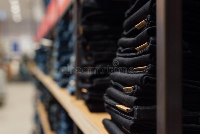 Куча джинсов на окне магазина в магазине Сложенные джинсы на полке стоковые изображения